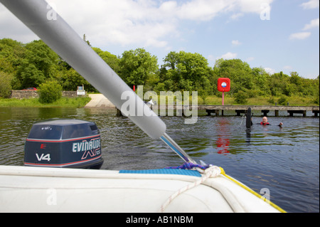 mid thirties male sitting in water with waterski next to jetty waiting for boat to start up to go waterskiing - Stock Photo