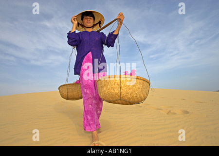Woman with conical hat carries flowers in pannier baskets across sand dunes near Mui Ne Vietnam - Stock Photo