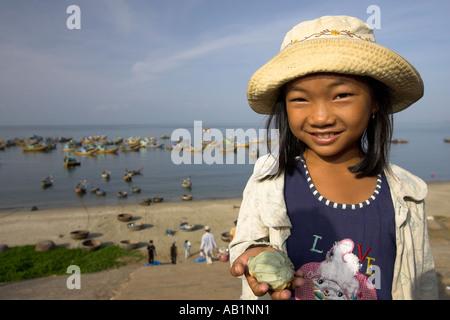 Young girl selling sea shells at Lang Chai fishing village near Mui Ne Vietnam - Stock Photo