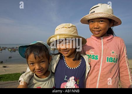 Young children at Lang Chai fishing village near Mui Ne selling sea shells Vietnam - Stock Photo