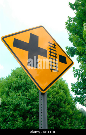 Train tracks and road intersection with both crossings marked on street sign in California America - Stock Photo