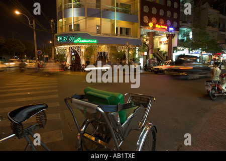 Cyclo rickshaw opposite popular Allez Boo bar and restaurant Pham Ngu Lao district Ho Chi Minh City Vietnam - Stock Photo