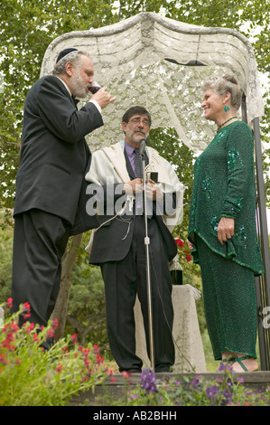 Wedding ceremony under a canopy with Rabbi bride and groom at a traditional Jewish wedding in Ojai CA - Stock Photo