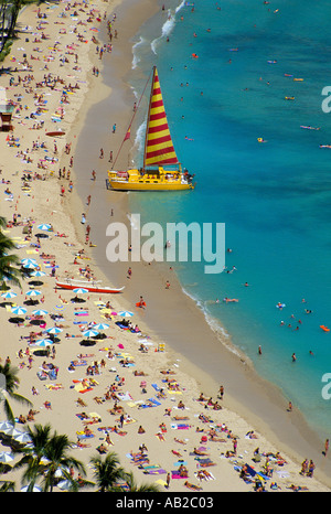 Looking down on Waikiki Beach Hawaii A yellow catamaran has pulled up on the sunbather filled beach - Stock Photo