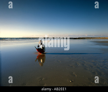 Man on empty beach with laptop computer and mobile phone - Stock Photo