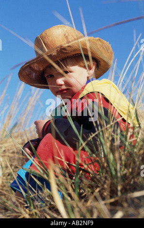 A small boy in a cowboy hat sitting in long grass - Stock Photo