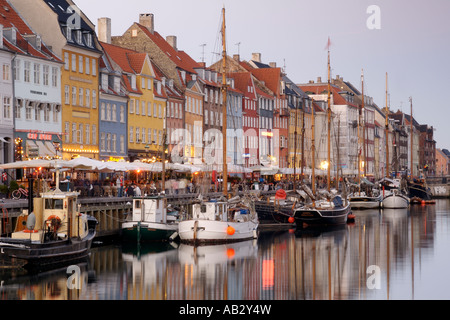 Boats and side-walk cafes along the Nyhavn canal in Copenhagen Denmark. - Stock Photo