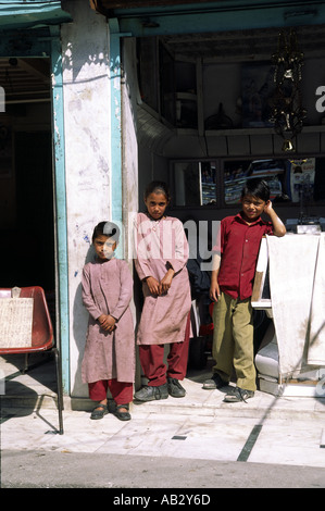 Schoolchildren stand in a shop doorway in Sarahan Himachal Pradesh India - Stock Photo
