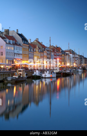 Boats and side-walk cafes along the Nyhavn canal in Copenhagen Denmark at dusk. - Stock Photo