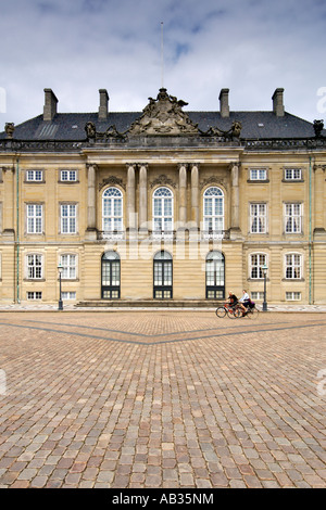 Two women cycling past Christian VIII's Palace, also known as Levetzau's Palace, at Amalienborg in Copenhagen Denmark. - Stock Photo