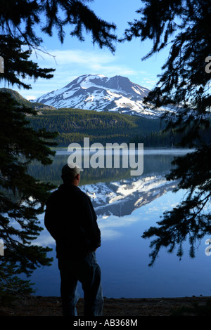 Man stands by lake looking at mountain - Stock Photo