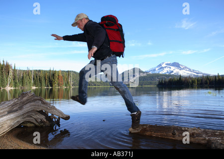 Man with backpack leaps across logs at Sparks Lake Oregon - Stock Photo