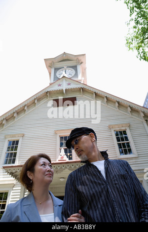 Senior couple standing in front of clock tower - Stock Photo