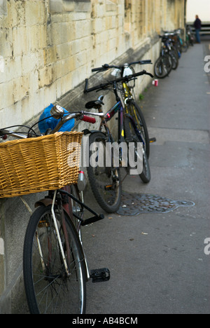 Row of black bicycles parked on pavement against building along street Oxford England - Stock Photo
