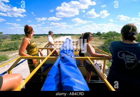 Tourists game viewing from the roof of an overland 4wd truck vehicle in Etosha National Park. - Stock Photo