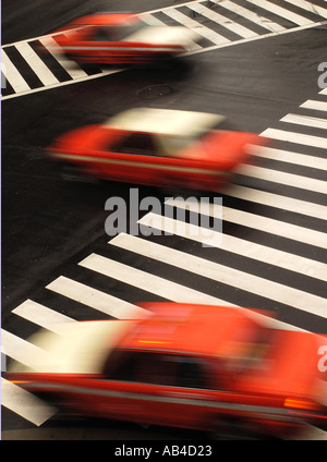 Red Tokyo taxis speeding across an intersection in Tokyo Japan 2006 - Stock Photo