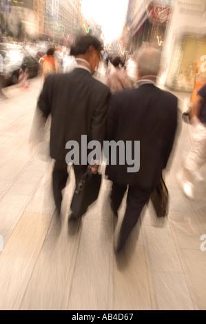 Businessmen walking on street with blurred slow shutter speed in Tokyo Japan - Stock Photo