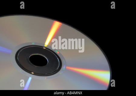 CD-ROM or DVD with rainbow reflections over a black background - Stock Photo
