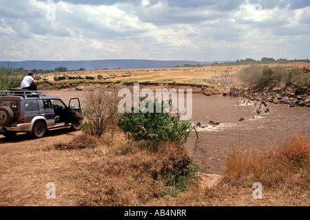 Tourists in a 4X4 watching zebras and wildebeest crossing the Mara river during the annual migration in Kenya. - Stock Photo