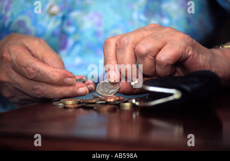 81 year old elderly woman counting her money, London, UK. - Stock Photo