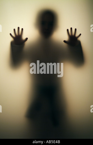 Boy 7, 8, 9, 10, 11, 12, 13, 14 years old  Figure behind transparent wall - Stock Photo