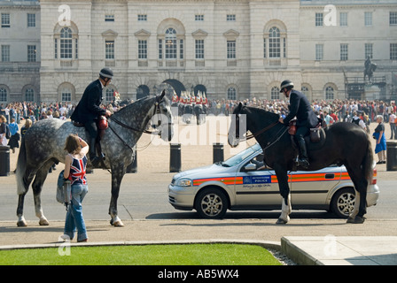 Horseguards parade mounted police on duty during changing the guard ceremony watched by pedestrian with union flag - Stock Photo