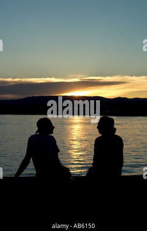 Couple sitting enjoying the sunset and talking July 2003 - Stock Photo
