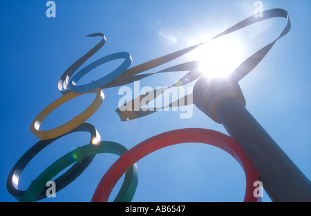 A sculpture of the Olympic Torch, the flame seemingly lit by the sun, with Olympic rings symbol, in Alimos, Athens, - Stock Photo