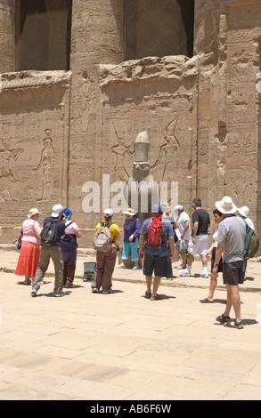 Tourist's admire the granite statue of the falcon headed god Horus at Egypt, Edfu Temple Egypt.The temple is dedicated to Horus Stock Photo