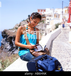 Young female tourist looking at a guide book listening on ipod in Santorini Greek Islands Greece  KATHY DEWITT - Stock Photo