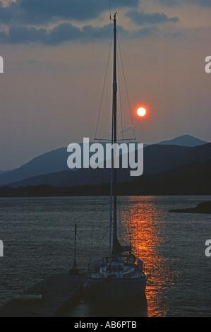 Yacht and jetty at sunset near Ballachulish on Loch Leven, Lochaber, Scotland, United Kingdom, Europe. - Stock Photo