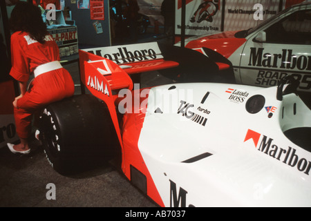 TAG McLaren F1 car of Niki Lauda on a motor show stand mid 1980s with shapely publicity girl perched on one rear - Stock Photo