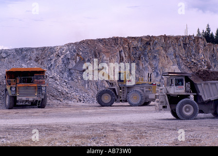 Front End Loader loading 100 Ton Mining Dump Trucks at Open Pit Limestone Quarry Mine on Texada Island British Columbia - Stock Photo