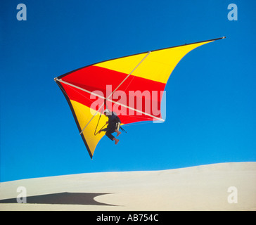 man taking off from sand dunes on a hang glider - Stock Photo