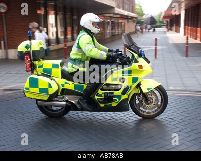 Chelmsford Essex ambulance service paramedic riding motorcycle over raised paving speed hump in town centre - Stock Photo
