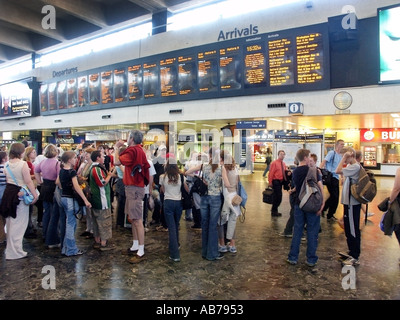 Euston Main Line Railway Station and terminal main concourse with arrival departure board school children with adult - Stock Photo
