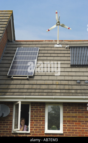 Micro Wind Turbine Solar Voltaic and Evacuated solar tubes on roof of house in Ferndown Dorset England - Stock Photo