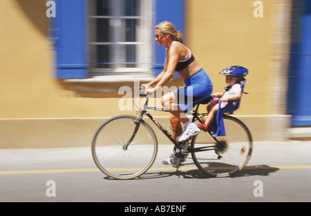 Mother and child biking past village home in Provence France   blue on yellow - Stock Photo