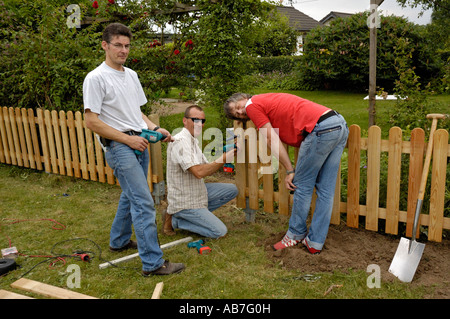Handymen building a garden fence on allotments in Germany. - Stock Photo