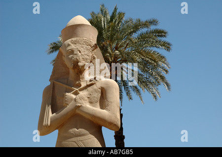 Granite statue of Rameses II with palm tree at Karnak Temple Egypt - Stock Photo