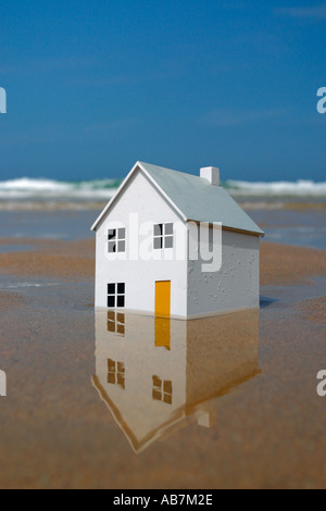 Model house sinking into the sand with ocean waves in the background - Stock Photo