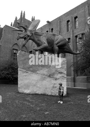 Child Stands next to Massive dinosaur sculpture outside the Yale Peabody museum - Stock Photo