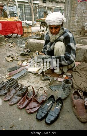 Pakistan Baluchistan Quetta old cobbler at work - Stock Photo