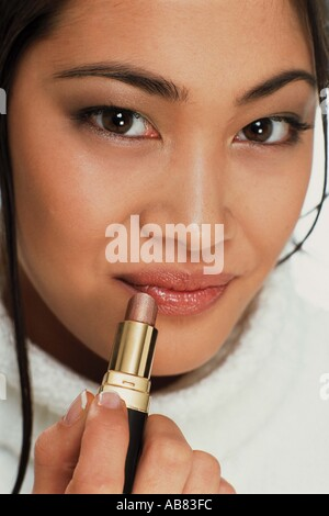Young woman applying lipstick - Stock Photo