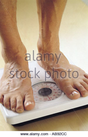 Man standing on scales - Stock Photo