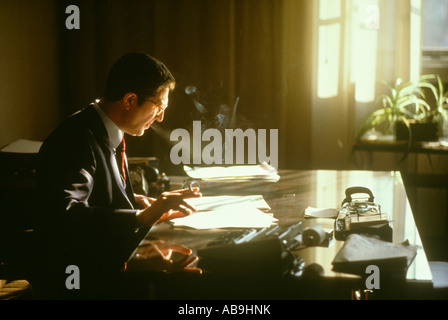 Italian businessman smoking at desk late afternoon sunlight window  office executive worker smoke smoking desk organize - Stock Photo