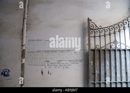 Warning sign written on the wall by a pipe and an iron gate - Stock Photo