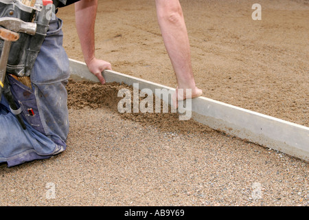 Leveling out sand with a metal plank - Stock Photo