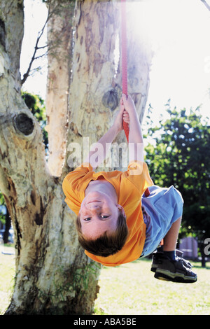 Boy swinging on a tree rope - Stock Photo