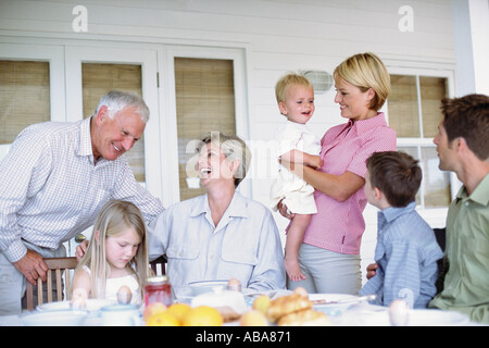 Three generations of a family eating together - Stock Photo